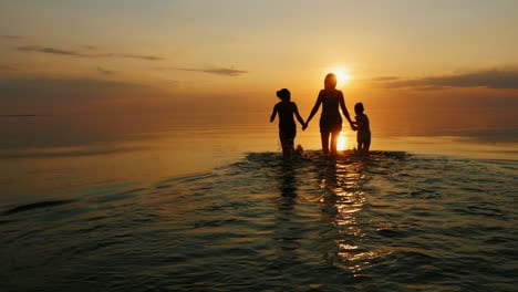 Mother-With-Two-Children-Go-Swimming-In-The-Sea-At-Sunset-Laughing