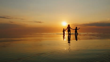 Mother-With-Two-Children-Laughing-In-The-Sea-At-Sunset-Out-Of-The-Water