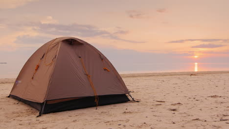 The-Tent-Is-In-The-Sand-On-The-Orange-Sea-And-Sunset-Background