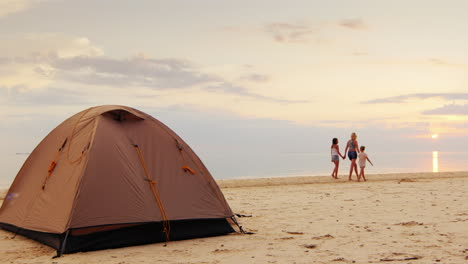 A-Woman-With-Her-Two-Daughters-Walking-Along-The-Seashore-In-The-Foreground-Is-A-Tent-For-The-Night