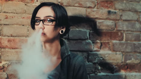 Gothic-Woman-With-Short-Black-Hair-Smokes-An-Electronic-Cigarette-On-A-Background-Of-A-Brick-Wall-In