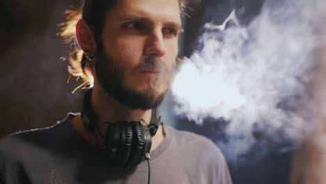 Young-Hipster-Man-Smokes-An-Electronic-Cigarette-Effectively-Produces-Steam-In-A-Beam-Of-Light-Slow-