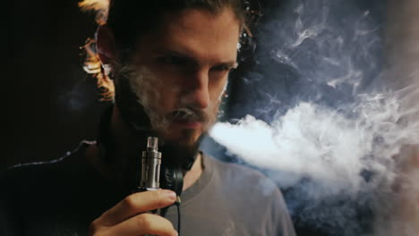 A-Young-Bearded-Man-Smoking-An-Electronic-Cigarette-Smoke-Comes-Out-Beautifully-In-A-Beam-Of-Light
