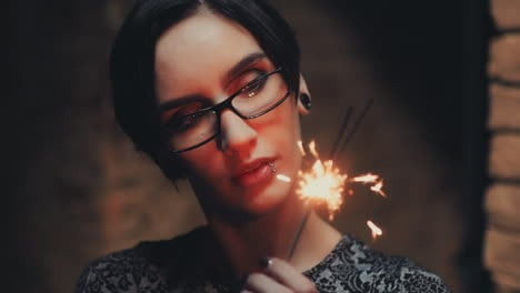 Portrait-Of-Young-Goth-Woman-With-Short-Black-Hair-Wearing-Glasses-He-Looks-At-A-Burning-Sparkler-Sl