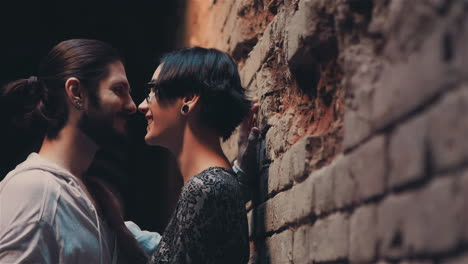 Young-Gothic-Hipster-Couple-Admiring-Each-Other-On-The-Background-Of-Brick-Wall