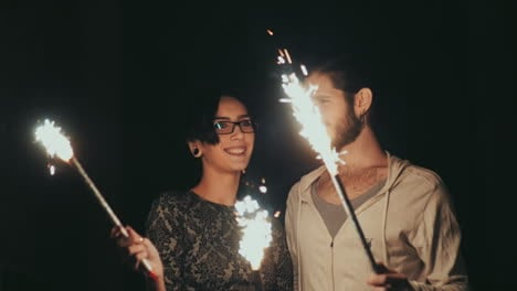 Young-Hipster-Couple-Having-Fun-With-Fireworks-In-The-Hands-Of