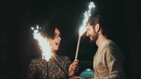 A-Young-Man-With-A-Beard-And-A-Brunette-Woman-Having-Fun-With-Fireworks-In-The-Hands-Of