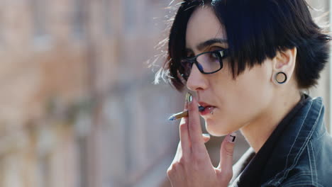 Young-Hipster-Woman-Smokes-By-The-Window-A-Little-Pensive-And-Sad
