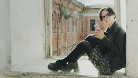 Young-Hipster-Woman-Sitting-On-A-Window-Sill-In-An-Old-Building-Using-Cell-Phone