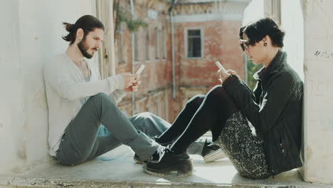 Young-Hipster-Couple-Sitting-At-The-Window-Use-Mobile-Phones-Concept---The-Lack-Of-Live-Communicatio