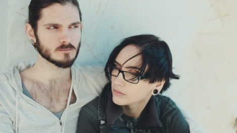 Thoughtful-Young-Hipster-Couple-They-Sit-Side-By-Side-On-The-Windowsill-Dream-Dark-Haired-Woman-With