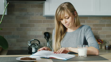 Young-Attractive-Woman-Reading-A-Book-In-The-Kitchen-Nearby-Stands-A-Glass-Of-Milk-Concept---Healthy