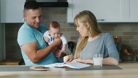 Young-Family-In-The-Kitchen-Mom-Reading-A-Book-With-The-Baby-Daddy-Is-Near