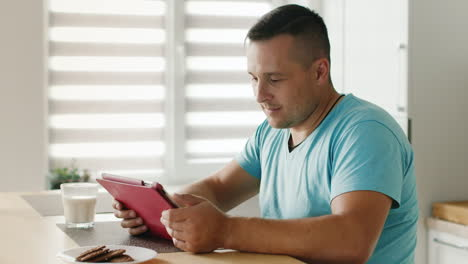 Young-Man-Reading-News-On-Digital-Tablet-Sitting-By-The-Window-In-His-Kitchen