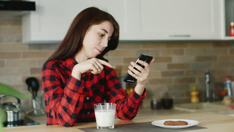 A-Young-Woman-Uses-A-Smartphone-He-Is-Sitting-In-His-Kitchen-Standing-Next-To-A-Glass-Of-Milk-Health