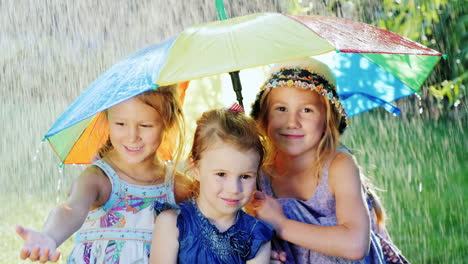 Three-Sisters-Are-Hiding-Under-The-Umbrella-Of-Color-There-Is-A-Warm-Summer-Rain-The-Children-Are-Ha