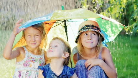 Three-Cheerful-Carefree-Girl-Under-The-Umbrella-Of-The-Rainbow-Colors-There-Is-A-Warm-Rain-Happy-Chi