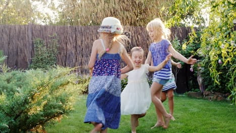 Four-Carefree-Children-Laughing-In-Garden-During-With-Streams-Of-Water