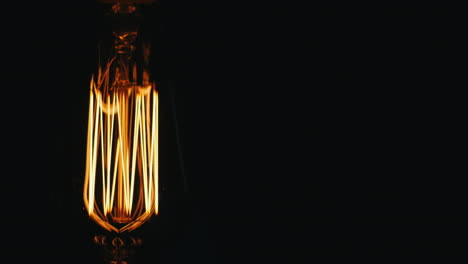 Oblong-Vintage-Lamp-Edison-Slowly-Turn-On-A-Black-Background-Prores-Hq-422-10-Bit-Video