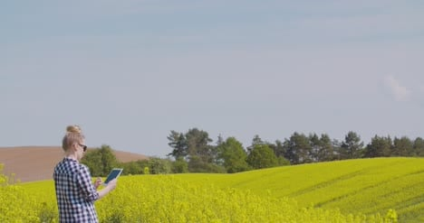 Farmer-Touching-Screen-Of-Digital-Tablet-At-Rapeseed-Field