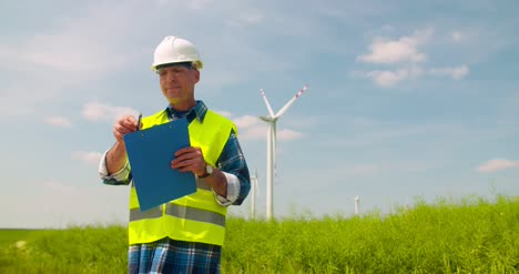 Engineer-Writing-On-Clipboard-While-Doing-Wind-Turbine-Inspection-7