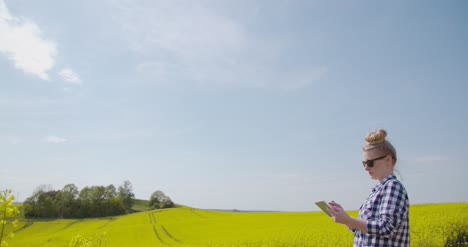 Farmer-Touching-Screen-Of-Digital-Tablet-At-Rapeseed-Field-1