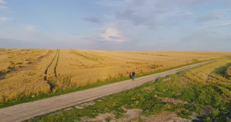 Male-Farm-Researcher-Standing-On-Dirt-Road-Amidst-Fields-6