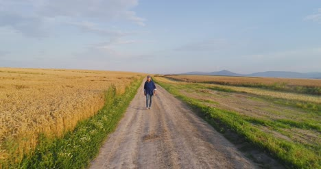 Male-Farm-Researcher-Standing-On-Dirt-Road-Amidst-Fields-3