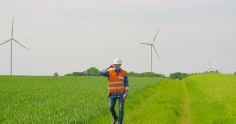 Engineer-Talking-On-Mobile-Phone-While-Walking-In-Farm-2