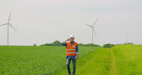 Smiling-Engineer-Using-Mobile-Phone-At-Farm-Against-Sky-1