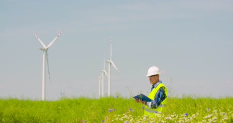 Engineer-Writing-On-Clipboard-While-Standing-Against-Windmill-9