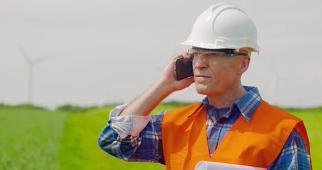 Engineer-Talking-On-Mobile-Phone-While-Walking-In-Farm-3