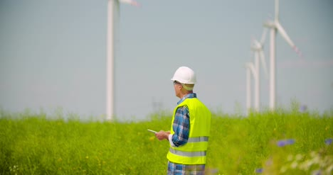 Engineer-Using-Digital-Tablet-While-Wind-Turbine-Inspection-At-Windmill-Farm-1