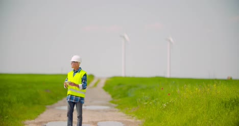 Engineer-Using-Digital-Tablet-While-Wind-Turbine-Inspection-At-Windmill-Farm-2
