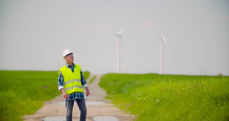 Engineer-Using-Digital-Tablet-While-Wind-Turbine-Inspection-At-Windmill-Farm-3