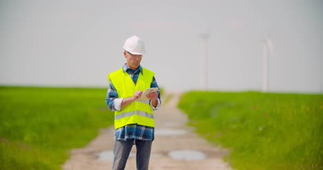 Engineer-Using-Digital-Tablet-While-Wind-Turbine-Inspection-At-Windmill-Farm-4