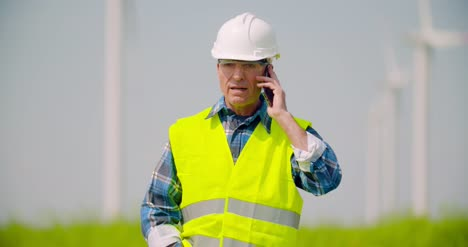 Engineer-Talking-On-Mobile-Phone-Against-Windmills-Farm