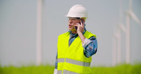 Angry-Engineer-Talking-On-Mobile-Phone-Against-Windmills-Farm