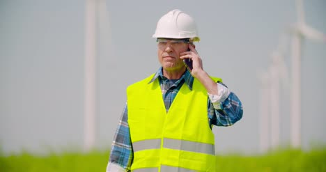 Angry-Engineer-Talking-On-Mobile-Phone-Against-Windmills-Farm-1