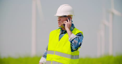 Angry-Engineer-Talking-On-Mobile-Phone-Against-Windmills-Farm-2