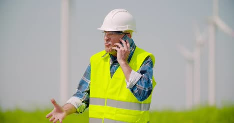 Angry-Engineer-Talking-On-Mobile-Phone-Against-Windmills-Farm-4
