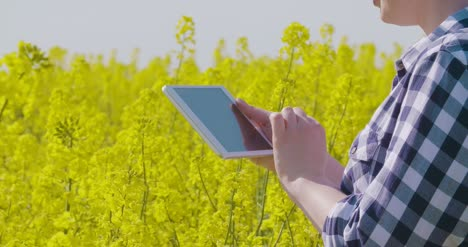 Farmer-Touching-Screen-Of-Digital-Tablet-At-Rapeseed-Field-21