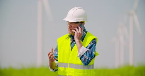 Angry-Engineer-Talking-On-Mobile-Phone-Against-Windmills-Farm-6