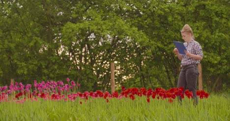 Female-Researcher-Walking-While-Examining-Tulips-At-Field-11