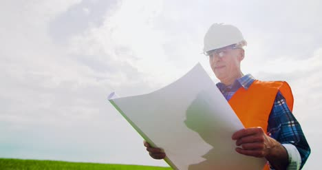 Engineer-Analyzing-Plan-While-Looking-At-Windmill-Farm-Eco-Energy-Concept-14