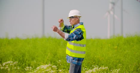 Engineer-Directing-By-Windmills-In-Farm-Against-Sky-1