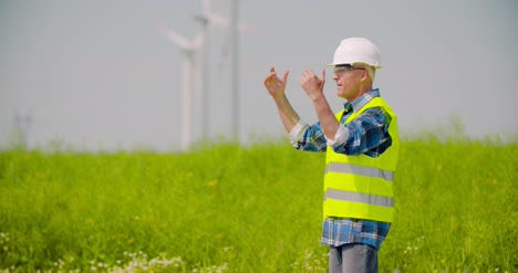 Engineer-Directing-By-Windmills-In-Farm-Against-Sky-2