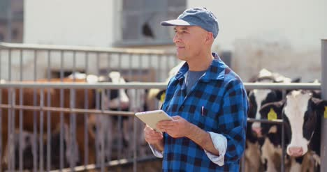 Farmer-Gesturing-While-Writing-On-Clipboard-Against-Barn-10
