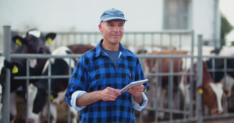 Farmer-Using-Digital-Tablet-While-Looking-At-Cows-13