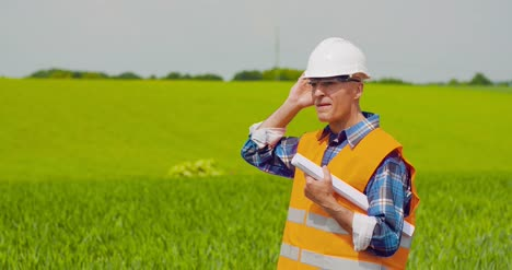 Engineer-Analyzing-Plan-While-Looking-At-Farm-6